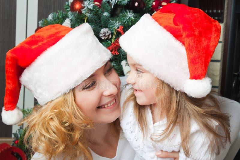 Szczęśliwa matka i córka w Santa kapeluszach zdjęcia royalty free