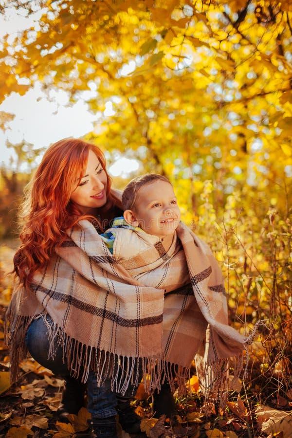 Szczęśliwa matka i jej mała zabawa w jesień lesie syna mieć i odprowadzenia fotografia royalty free