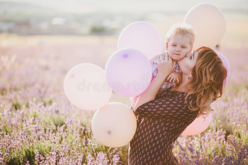 Szczęśliwa matka i jej mały syn pozuje z kolorowymi balonami w lawendy polu zdjęcie stock