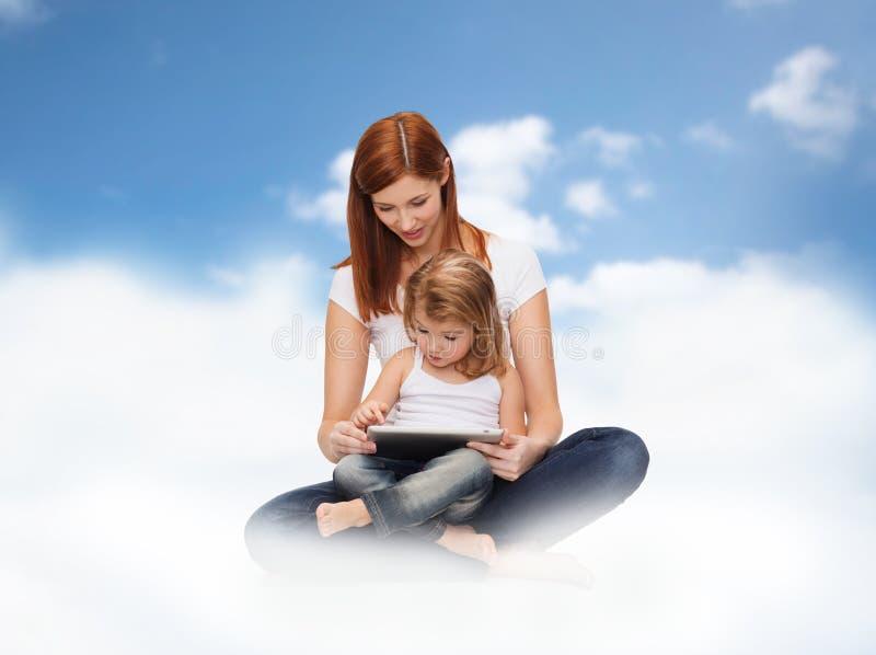 Szczęśliwa matka i mała dziewczynka z pastylka komputerem osobistym zdjęcia stock