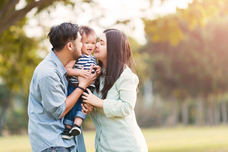 Szczęśliwa matka i ojciec całuje jego małego syna w parku fotografia royalty free
