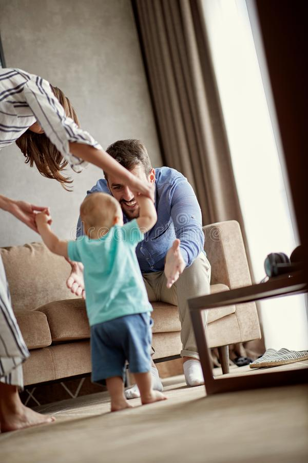 Szczęśliwa matka i ojciec w domu uczymy się chodzić ich dziecko chłopiec t zdjęcia stock