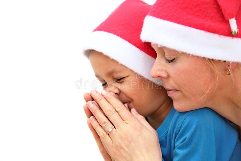 Szczęśliwa matka i syn patrzeje naprzód boże narodzenia i ono modli się obraz stock