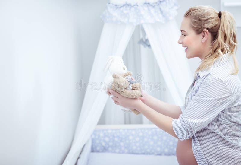 Szczęśliwa matka przygotowywa dziecka ` s pokój fotografia stock