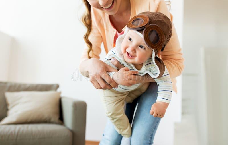 Szczęśliwa matka z dzieckiem jest ubranym pilotowego kapelusz w domu obrazy royalty free