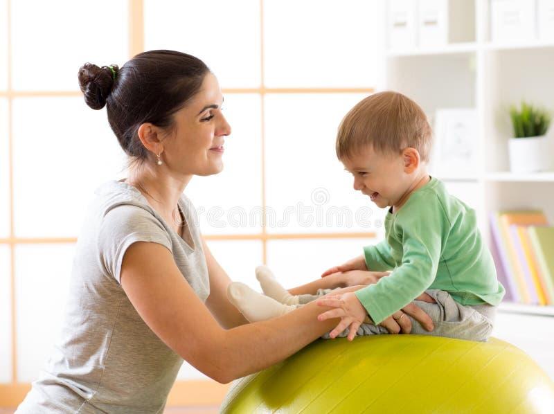 Szczęśliwa matka z dzieckiem robi gimnastykom na dużej sprawności fizycznej piłce w gym obraz stock
