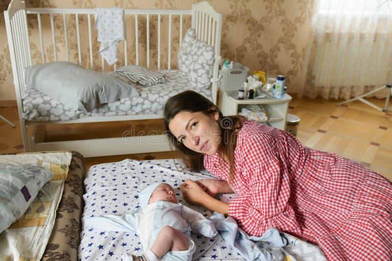 Szczęśliwa matka z dzieckiem w domu. MÅ'oda matka trzyma swoje noworodki. Kobieta i nowonarodzony chÅ'opiec spoczywajÄ… w sypial zdjęcia stock