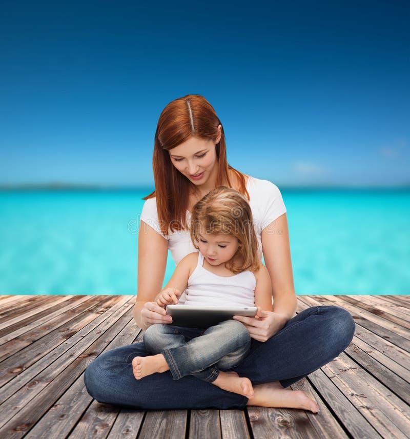 Szczęśliwa matka z małej dziewczynki i pastylki komputerem osobistym obrazy royalty free