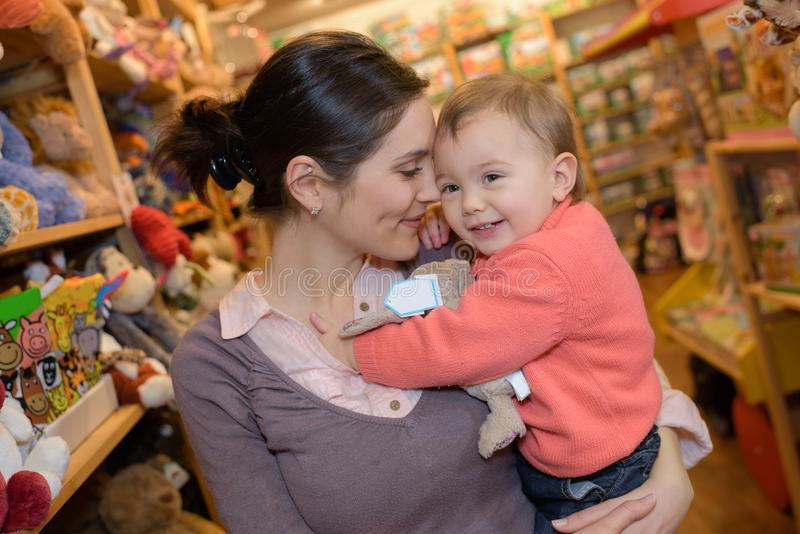 Szczęśliwa matka z radosną córką przy zabawkarskim sklepem obrazy royalty free