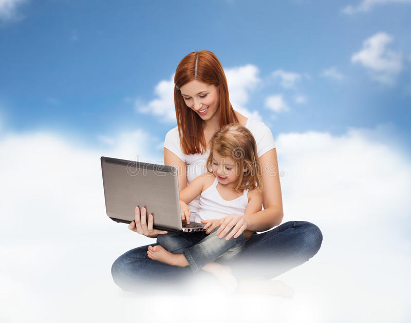 Szczęśliwa matka z uroczą małą dziewczynką i laptopem fotografia stock