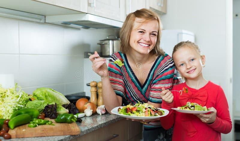 Szczęśliwa matki i dzieciaka łasowania warzywa sałatka zdjęcie stock
