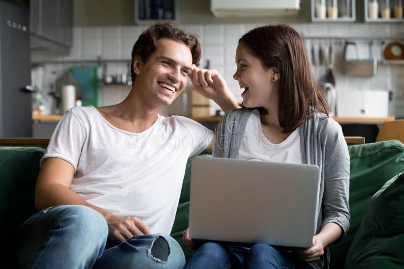 Szczęśliwa millennial para śmia się używać laptop na kitche wpólnie zdjęcia stock