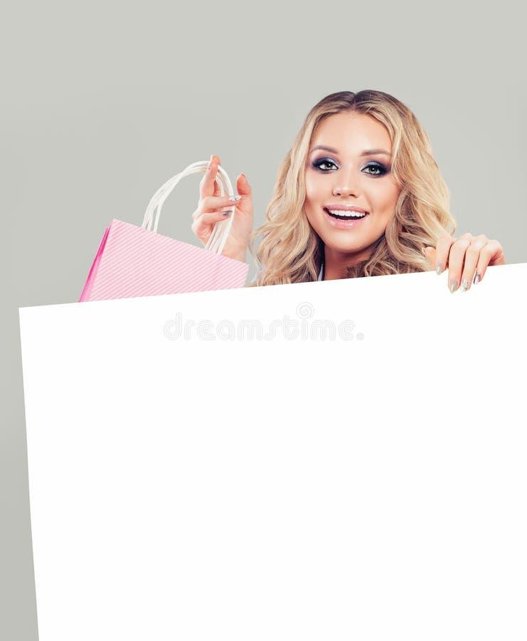 Szczęśliwa mody kobieta pokazuje torba na zakupy i biel pusta deska zdjęcie stock