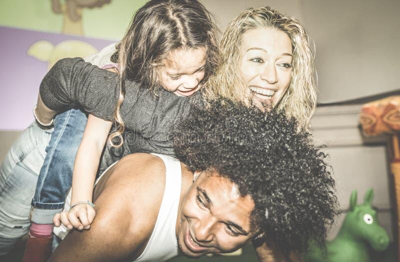 Szczęśliwa multiracial mama i tata bawić się z mieszaną biegową córką obraz stock