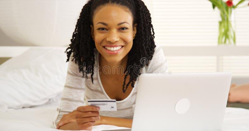 Szczęśliwa murzynka ono uśmiecha się z laptopem i kredytową kartą na łóżku obraz royalty free