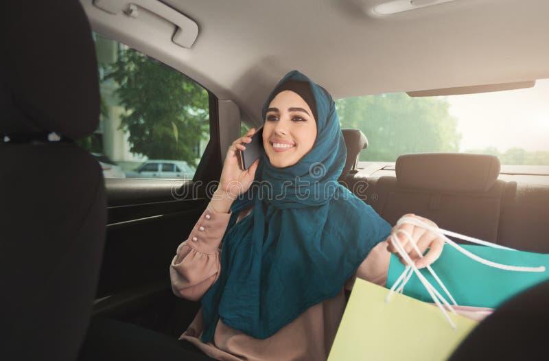 Szczęśliwa muzułmańska kobieta opowiada na smartphone w samochodzie zdjęcie royalty free