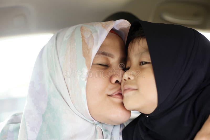 Szczęśliwa Muzułmańska mama i córka, azjata matka całujemy jej dziewczynki obrazy stock