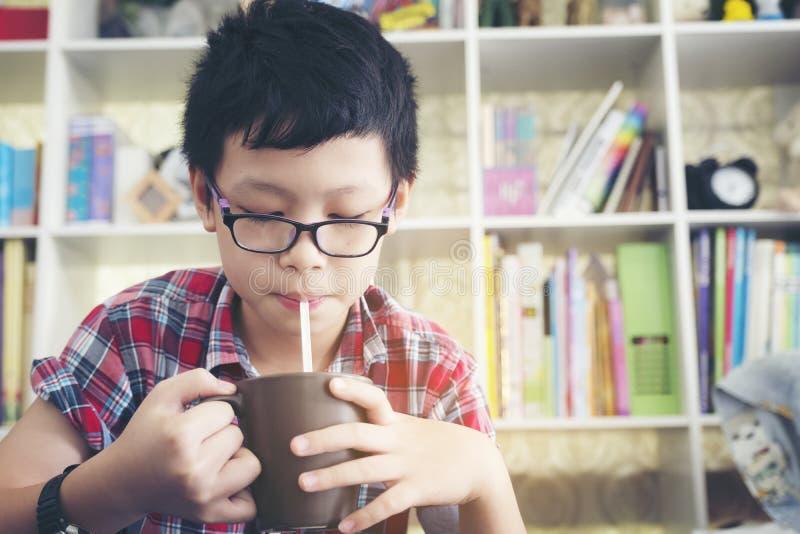 Szczęśliwa nastolatek chłopiec pije milkshake koktajl od słomy si zdjęcie stock
