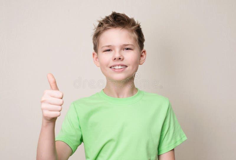 Szczęśliwa nastoletnia chłopiec z usuwalnym stomatologicznym brasem pokazuje kciuk w górę gest obrazy stock