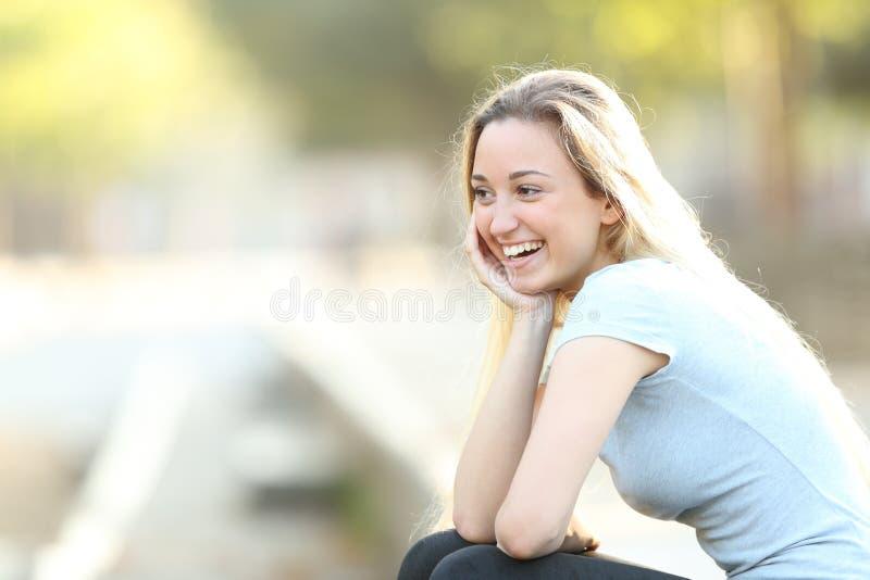 Szczęśliwa nastoletnia dziewczyna śmia się patrzeć daleko od w parku fotografia stock