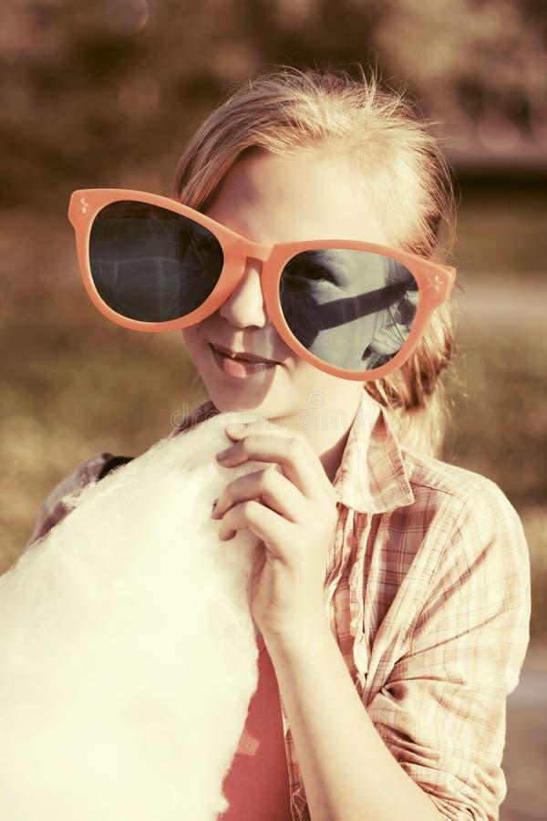 Szczęśliwa nastoletnia dziewczyna je bawełnianego cukierek plenerowego w okularach przeciwsłonecznych zdjęcia stock