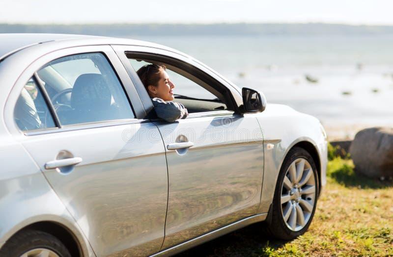 Szczęśliwa nastoletnia dziewczyna lub młoda kobieta w samochodzie obraz stock