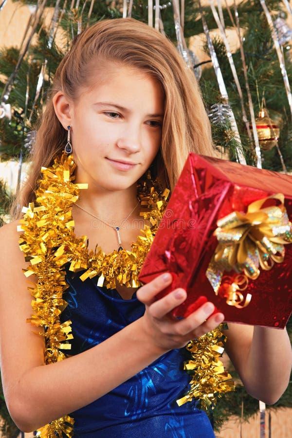 Szczęśliwa nastoletnia dziewczyna patrzeje nad jej Bożenarodzeniowym prezentem obrazy stock