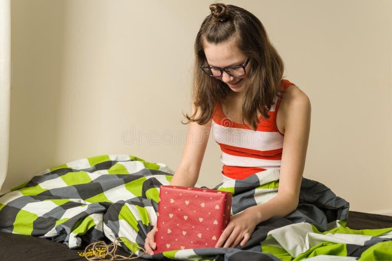 Szczęśliwa nastoletnia dziewczyna siedzi w łóżku z prezenta pudełkiem w domu zdjęcie stock
