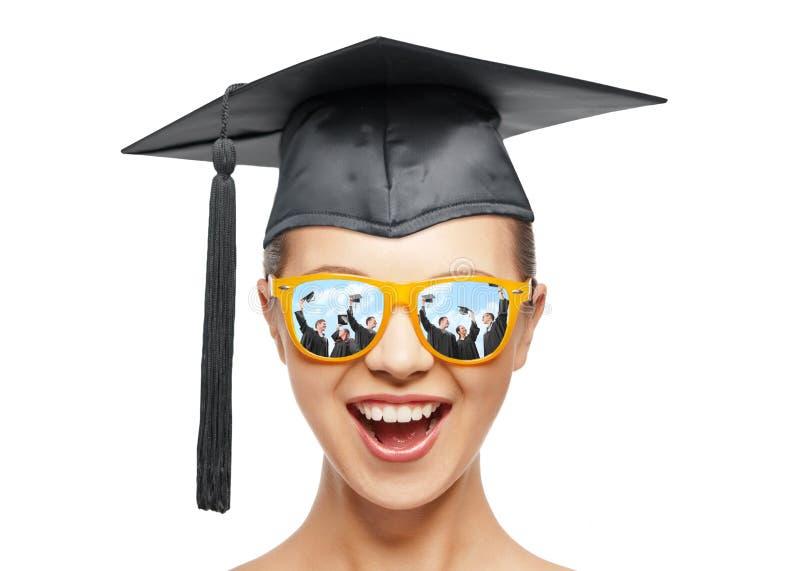 Szczęśliwa nastoletnia dziewczyna w cieniach i mortarboard kapeluszu fotografia stock