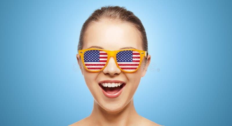 Szczęśliwa nastoletnia dziewczyna w cieniach z flaga amerykańską fotografia stock