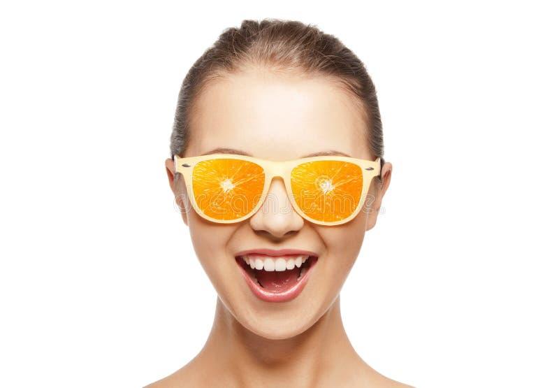 Szczęśliwa nastoletnia dziewczyna w okularach przeciwsłonecznych z pomarańczami zdjęcia royalty free