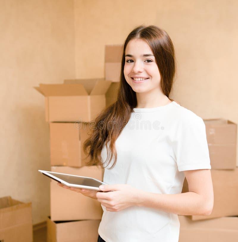 Szczęśliwa nastoletnia dziewczyna z pastylki komputerową pozycją na tle pudełka obrazy stock