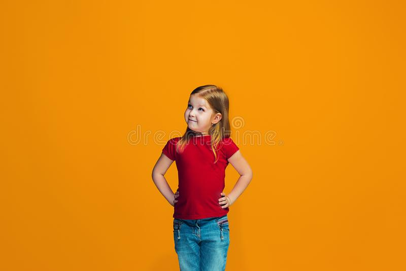 Szczęśliwa nastoletnia dziewczyny pozycja i ono uśmiecha się przeciw pomarańczowemu tłu obrazy royalty free