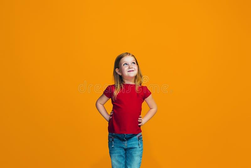 Szczęśliwa nastoletnia dziewczyny pozycja i ono uśmiecha się przeciw pomarańczowemu tłu zdjęcie royalty free