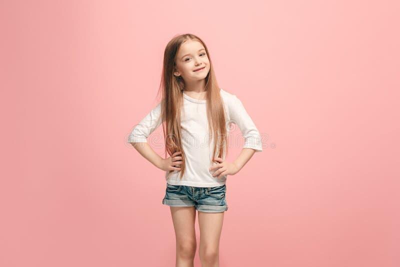 Szczęśliwa nastoletnia dziewczyny pozycja i ono uśmiecha się przeciw różowemu tłu zdjęcie royalty free