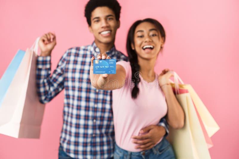Szczęśliwa nastoletnia para z torbami na zakupy i kartą kredytową zdjęcia royalty free