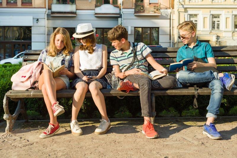 Szczęśliwa 4 nastoletniej przyjaciół lub szkoła średnia uczni czytelniczej książki siedzi na ławce w mieście zdjęcia royalty free