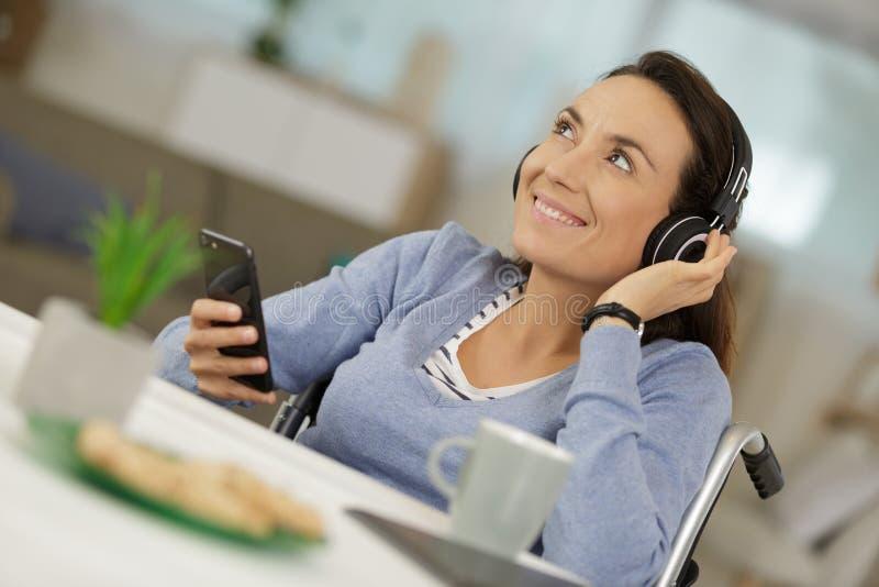 Szczęśliwa niepełnosprawna kobieta ono uśmiecha się podczas gdy trzymający telefon zdjęcie stock
