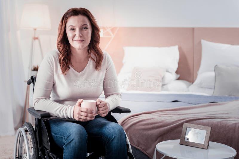 Szczęśliwa niepełnosprawna kobieta pije kawę obraz stock