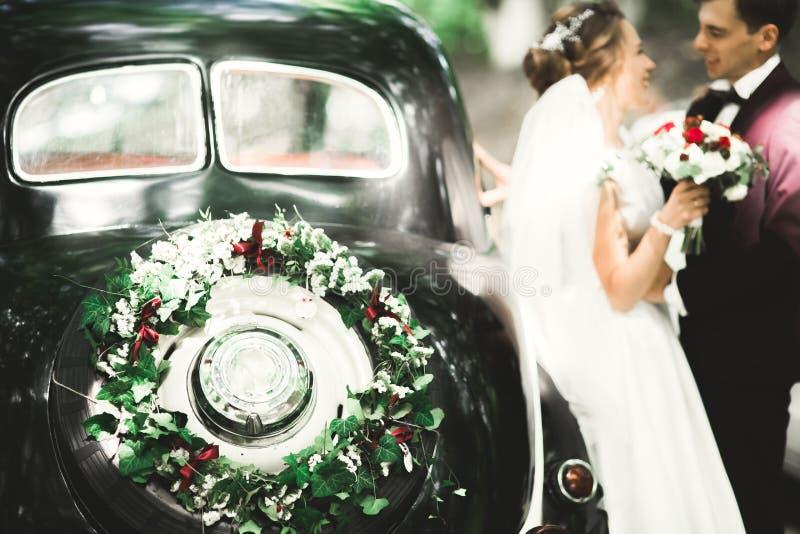 Szczęśliwa nowożeńcy para, mężczyzna i żona całuje blisko eleganckiego retro samochodu, fotografia stock