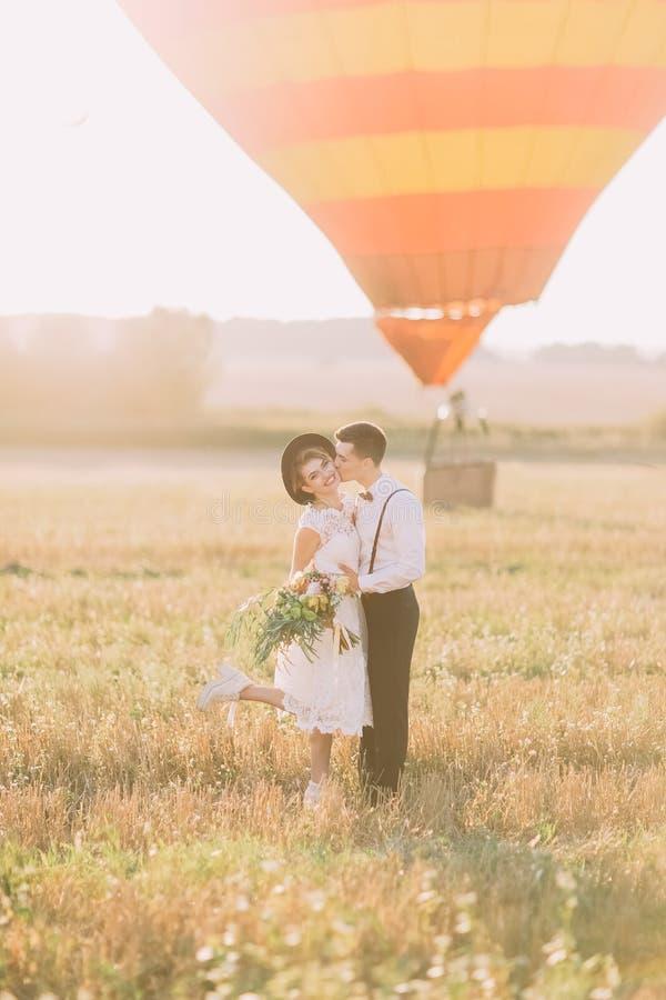 Szczęśliwa nowożeńcy para ma zabawę w pogodnym polu Fornal całuje rocznik ubierającej panny młodej w policzku przy zdjęcia stock