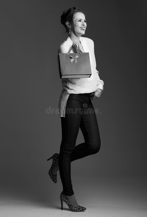 Szczęśliwa nowożytna elegancka kobieta patrzeje na boku z torba na zakupy zdjęcia royalty free