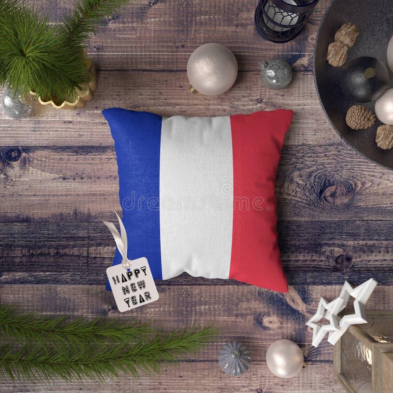 Szczęśliwa nowy rok etykietka z Francja flagą na poduszce Bo?enarodzeniowy dekoracji poj?cie na drewnianym stole z uroczymi przed fotografia royalty free