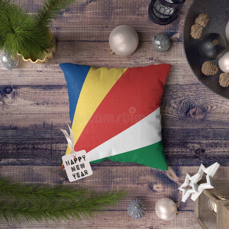 Szcz??liwa nowy rok etykietka z Seychelles zaznacza na poduszce Bo?enarodzeniowy dekoracji poj?cie na drewnianym stole z uroczymi obraz stock