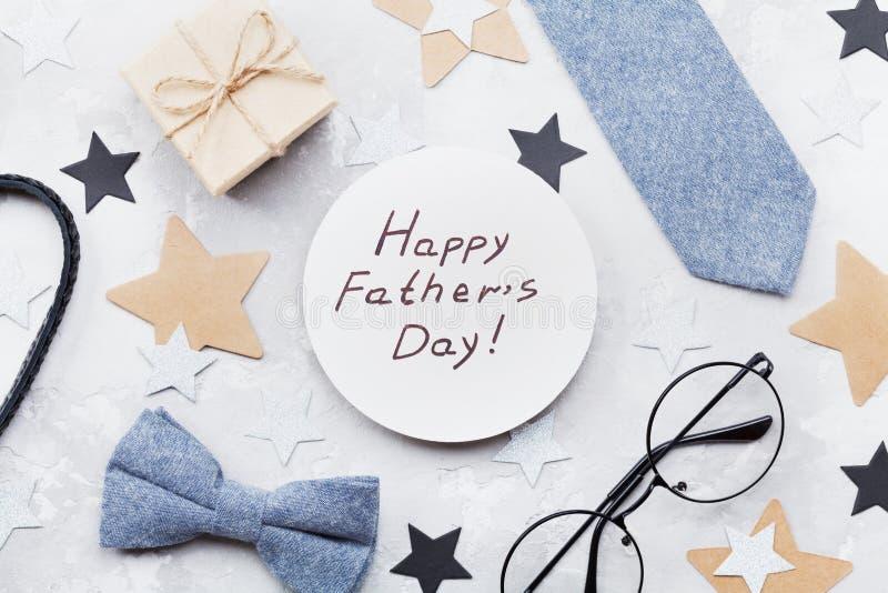 Szczęśliwa ojca dnia karta dekorował bowtie, krawat, eyeglasses, prezenta pudełko i gwiazdy na kamiennym stołowym odgórnym widoku