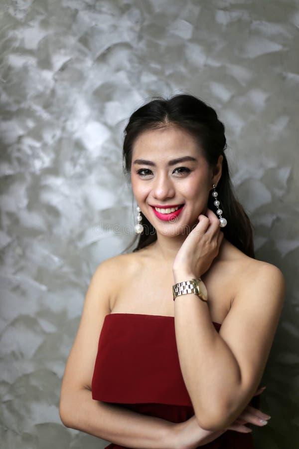 Szczęśliwa ono uśmiecha się piękna młoda seksowna kobieta w czerwonej partyjnej sukni zdjęcie stock
