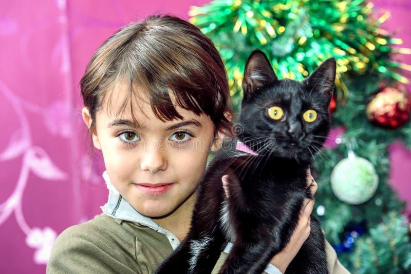 Szczęśliwa osiem roczniaka dziewczyna z czarnym kotem dla Bożenarodzeniowego prezenta zdjęcia royalty free