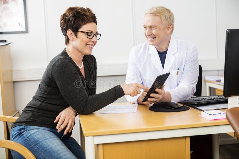 Szczęśliwa pacjenta I samiec lekarka Komunikuje Nad Cyfrowej pastylką obrazy stock
