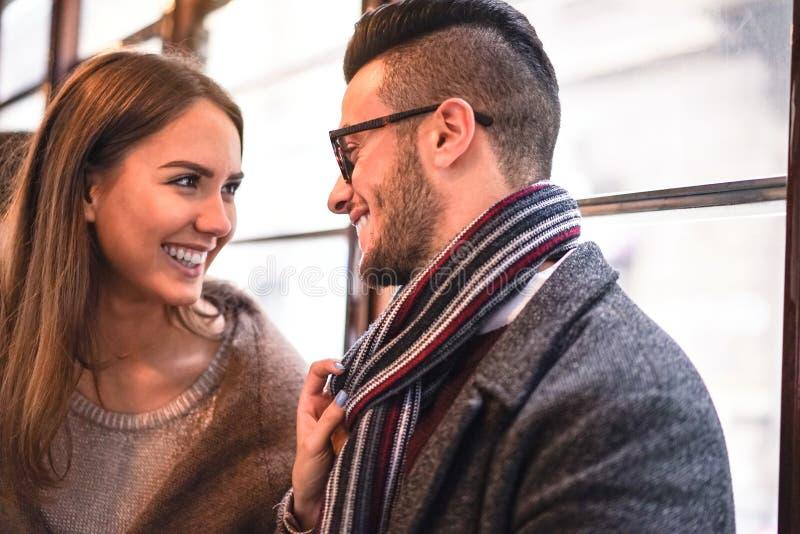 Szczęśliwa para śmia się podczas gdy patrzejący each inny w autobusie - Młoda piękna kobieta ciągnie jej chłopaka szalikiem obok  obraz stock