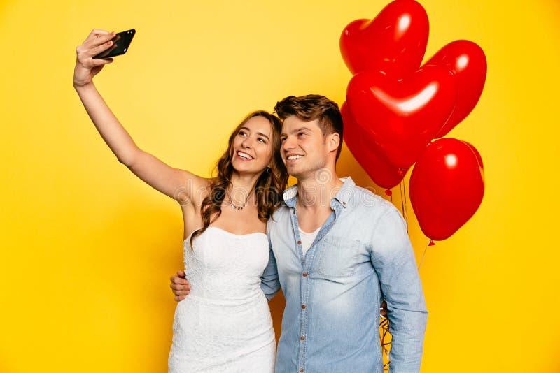 Szczęśliwa para bierze selfie na smartphone podczas gdy świętujący walentynki ` s dzień zdjęcia royalty free